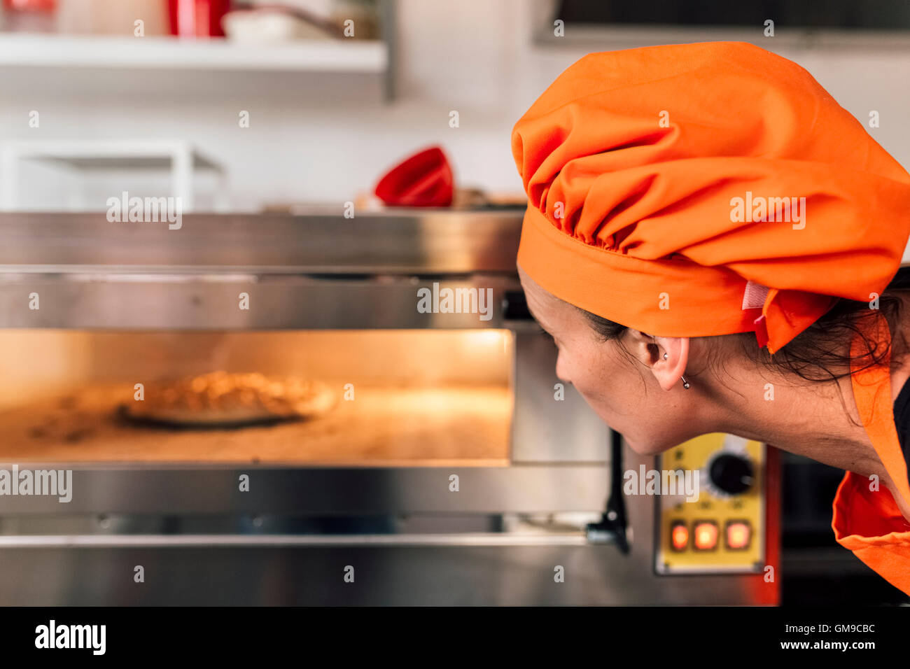 Pizza baker looking into oven - Stock Image