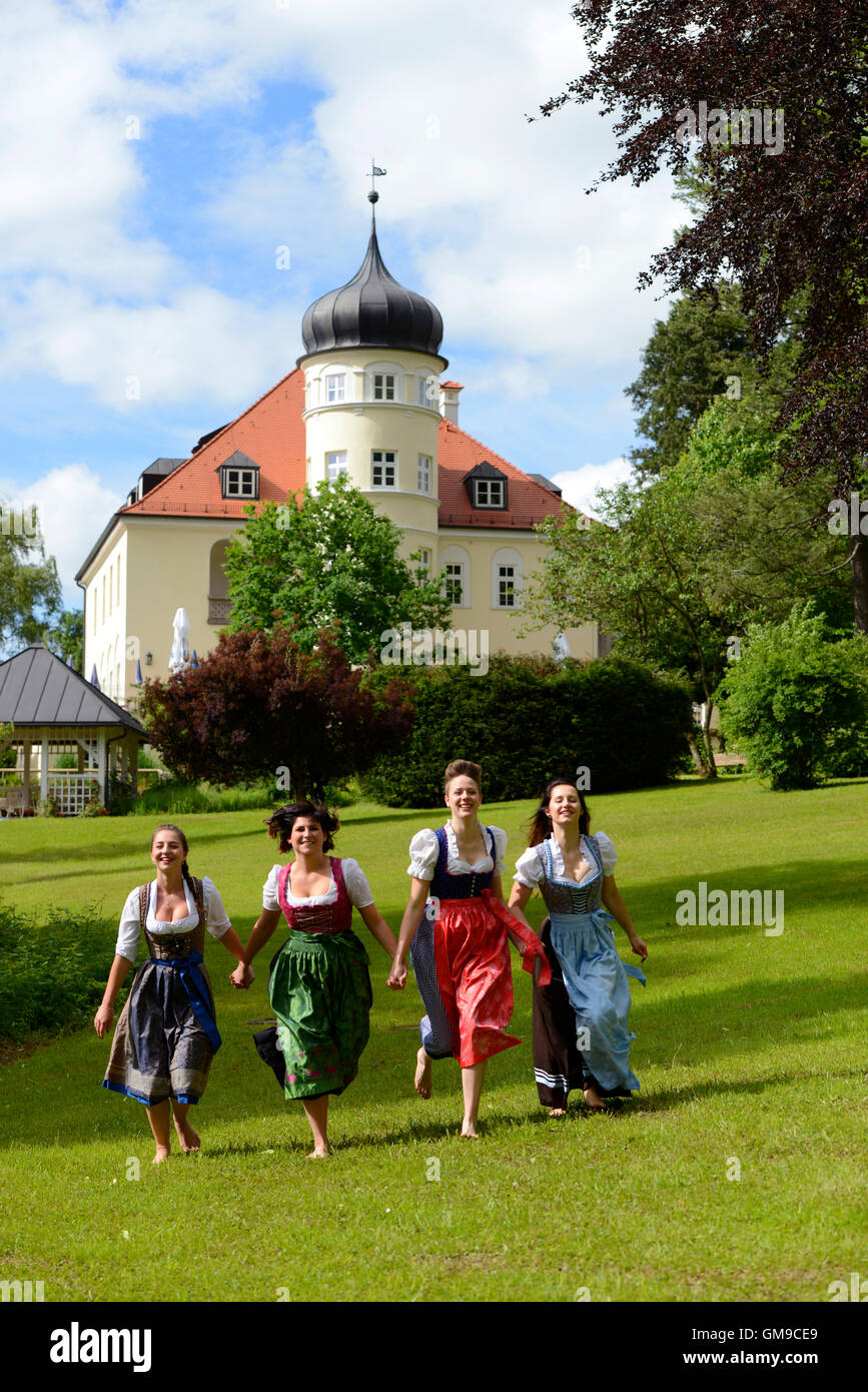 Germany, Bad Heilbrunn, four happy women wearing dirndls running hand in hand on a meadow - Stock Image