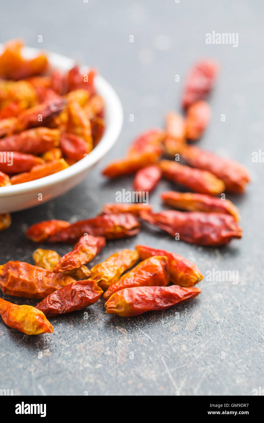 Dried mini chili peppers on kitchen table. - Stock Image