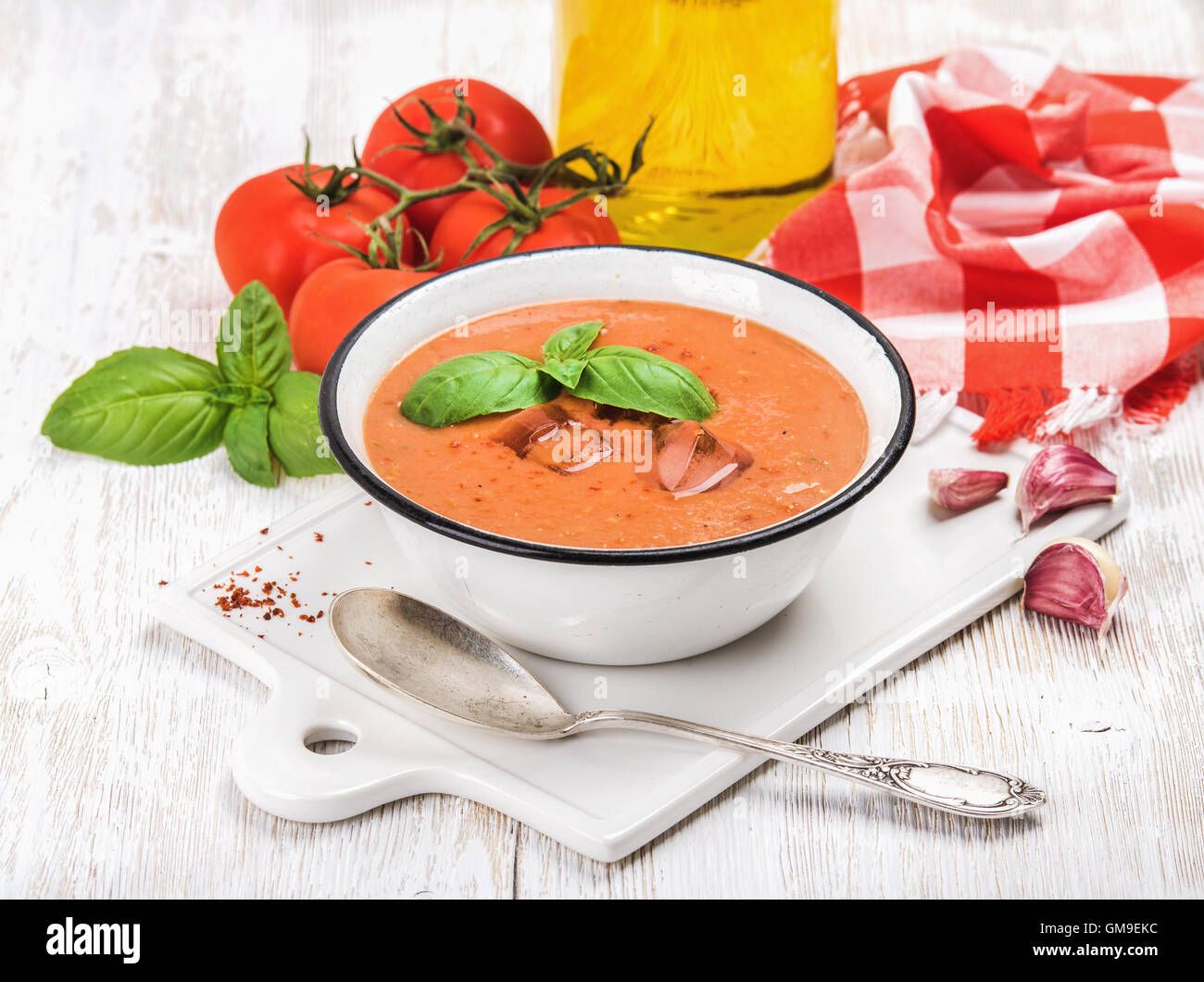 Cold gazpacho soup with ice, basil and fresh tomatoes - Stock Image