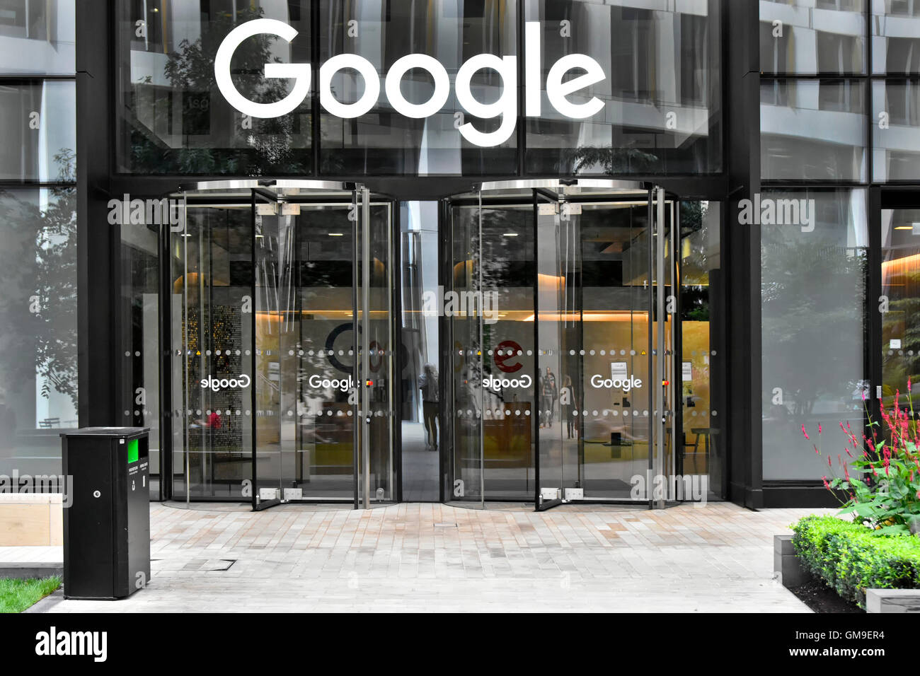 Glass doors to Google offices with sign above revolving entrance door to new office block in Kings Cross London - Stock Image