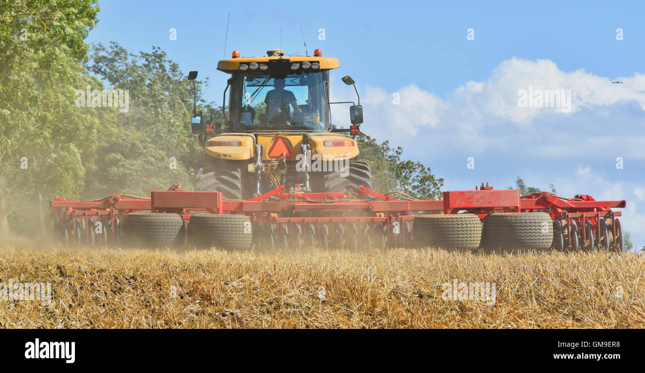 Vaderstad Rexius cultivator equipment working behind a Caterpillar Challenger tractor cultivating dry dusty clay - Stock Image