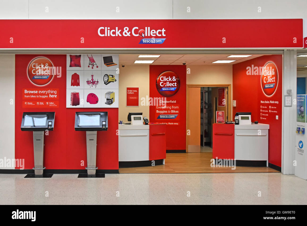 UK Tesco customer service in store Click and Collect counter using online internet browsing and provides customers - Stock Image
