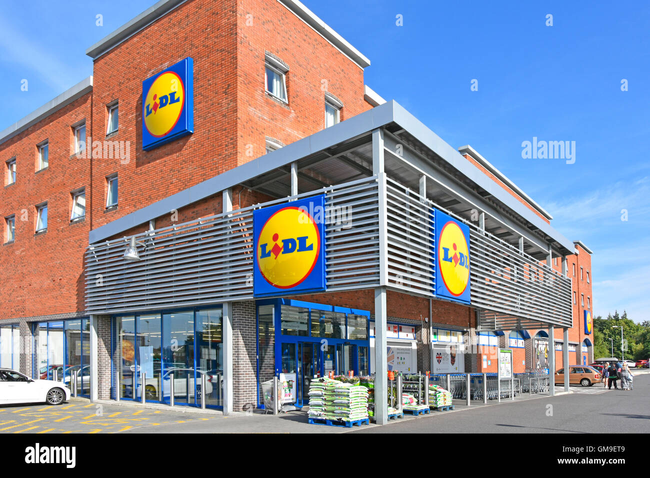 Exterior Lidl UK covered entrance to modern supermarket store on corner site with three logo panels in Tamworth - Stock Image
