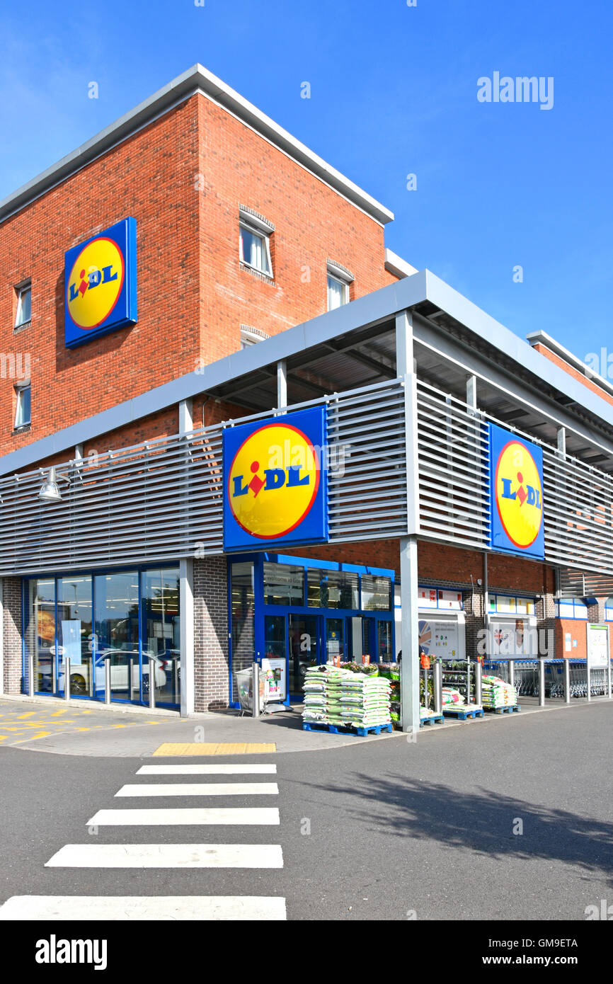 Exterior Lidl UK pedestrian crossing to entrance modern supermarket store on corner site with three logo panels - Stock Image