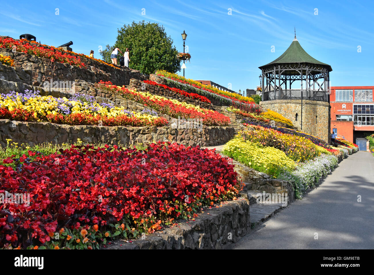 Summer flowers display on terraced embankment in public park gardens beside bandstand in Castle Grounds Tamworth - Stock Image