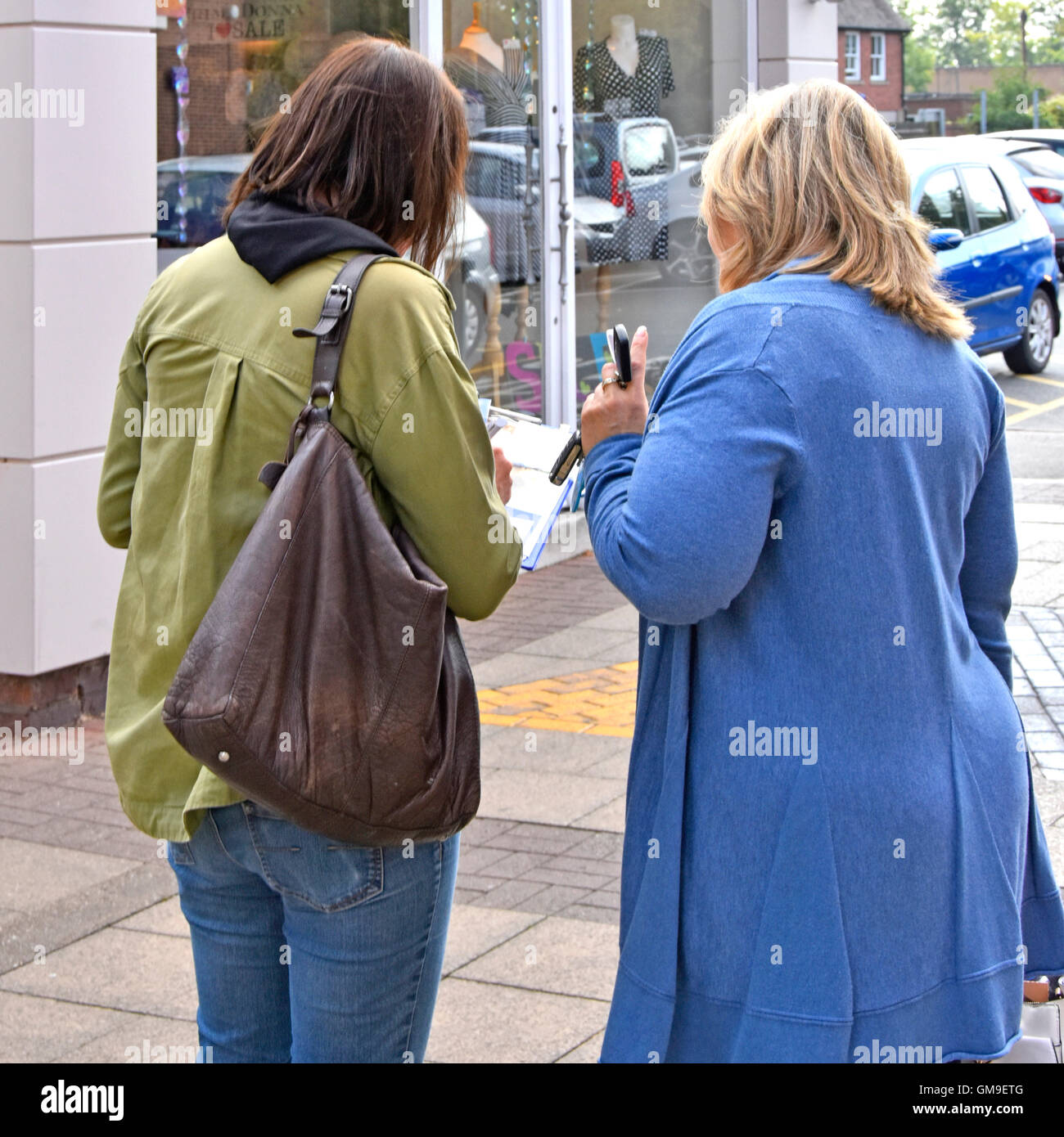 Woman holding clipboard (data entered blurred) interview questioning woman shopper small UK town centre street market - Stock Image