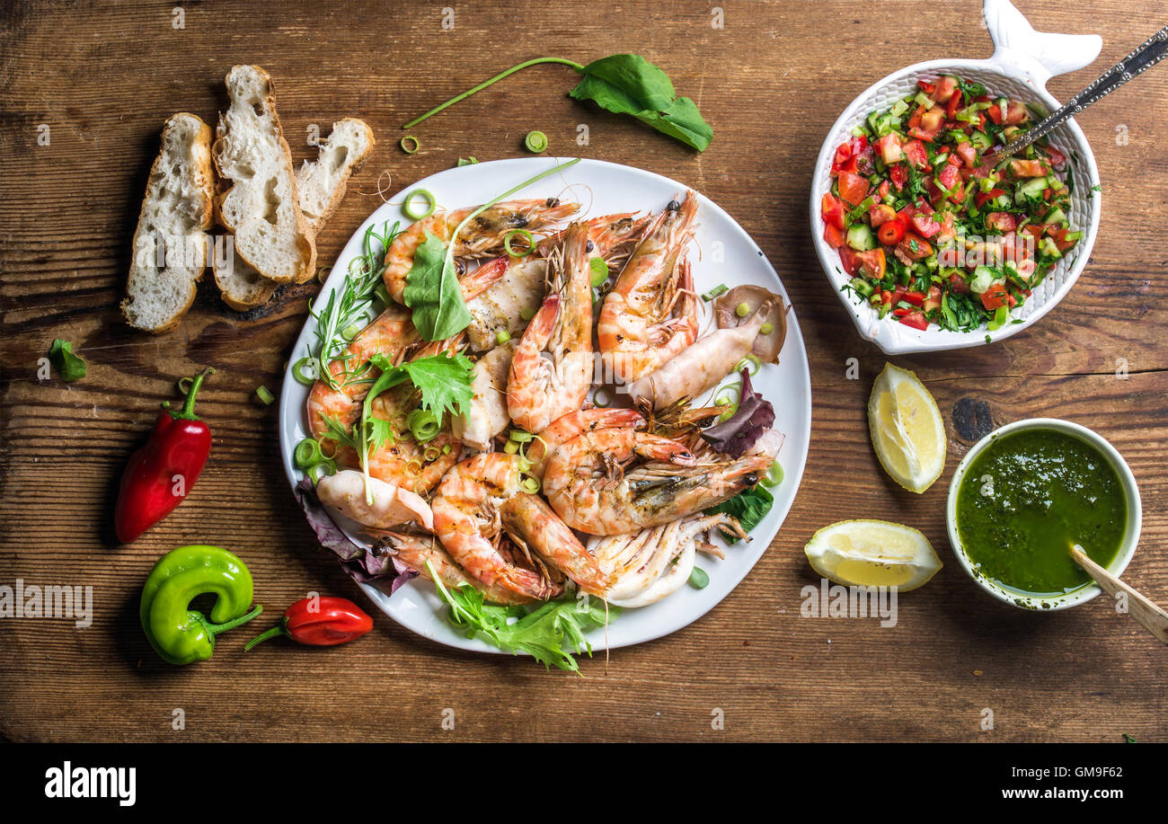 Plate of roasted seafood with fresh leek, green salad, peppers, lemon, bread, pesto sauce over wooden background, - Stock Image