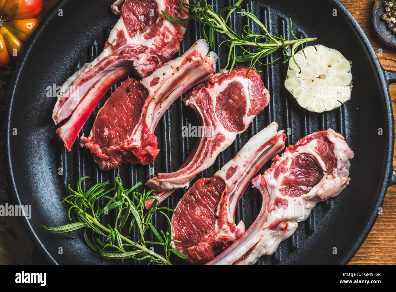Raw uncooked lamb meat chops with rosemary and garlic - Stock Image