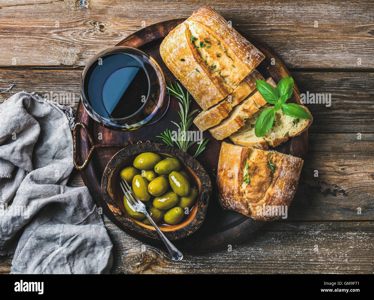 Red wine glass, green olives and ciabatta over wooden background - Stock Image