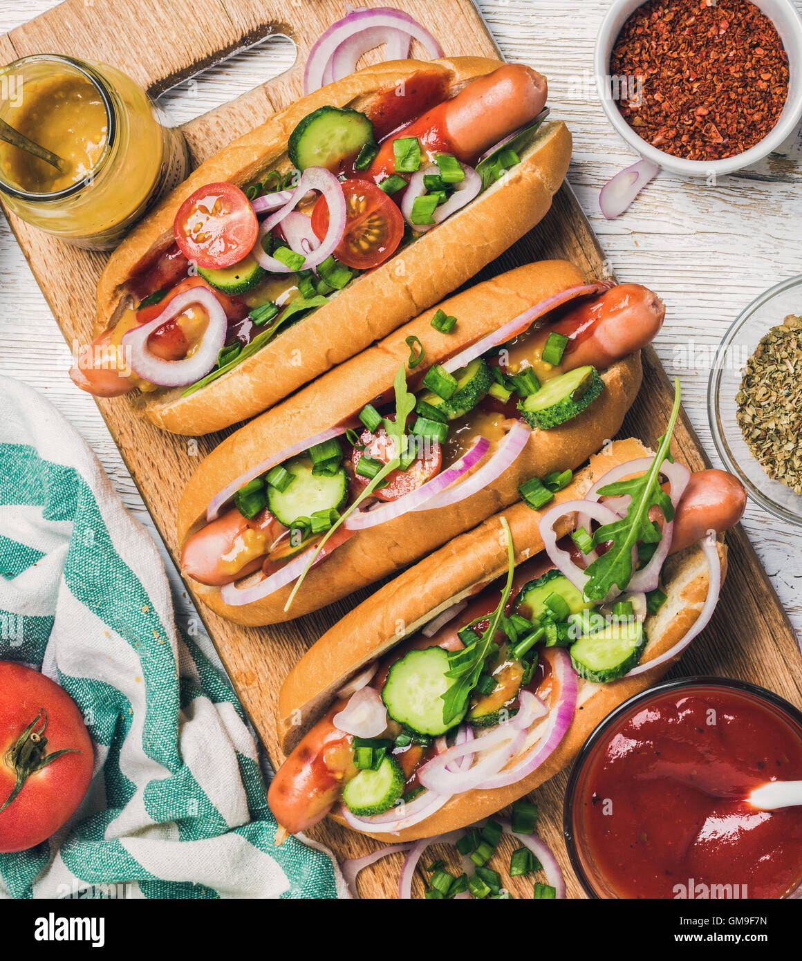Homemade hot-dogs with vegetables, ketchup, mustard and spices - Stock Image