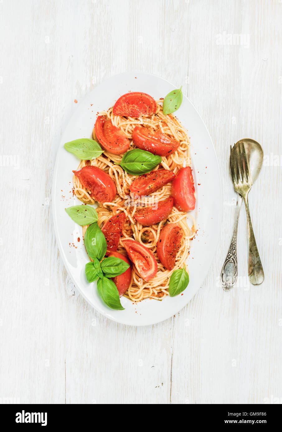 Pasta with roasted tomatoes and basil over white wooden background - Stock Image