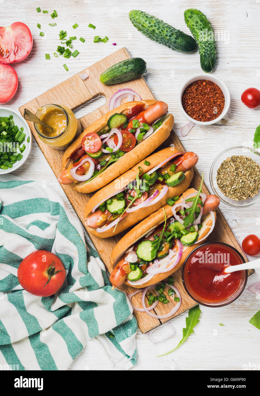 Homemade hot-dogs with fresh vegetables and spices over white background - Stock Image