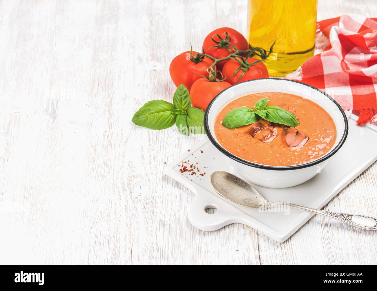Cold gazpacho soup with ice, basil and tomatoes, copy space - Stock Image