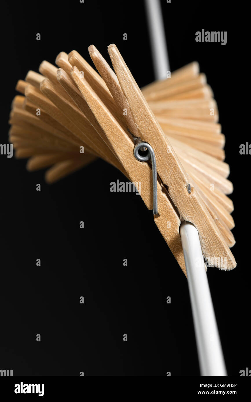 Wooden clothespins in fan shape to a white thread - Stock Image
