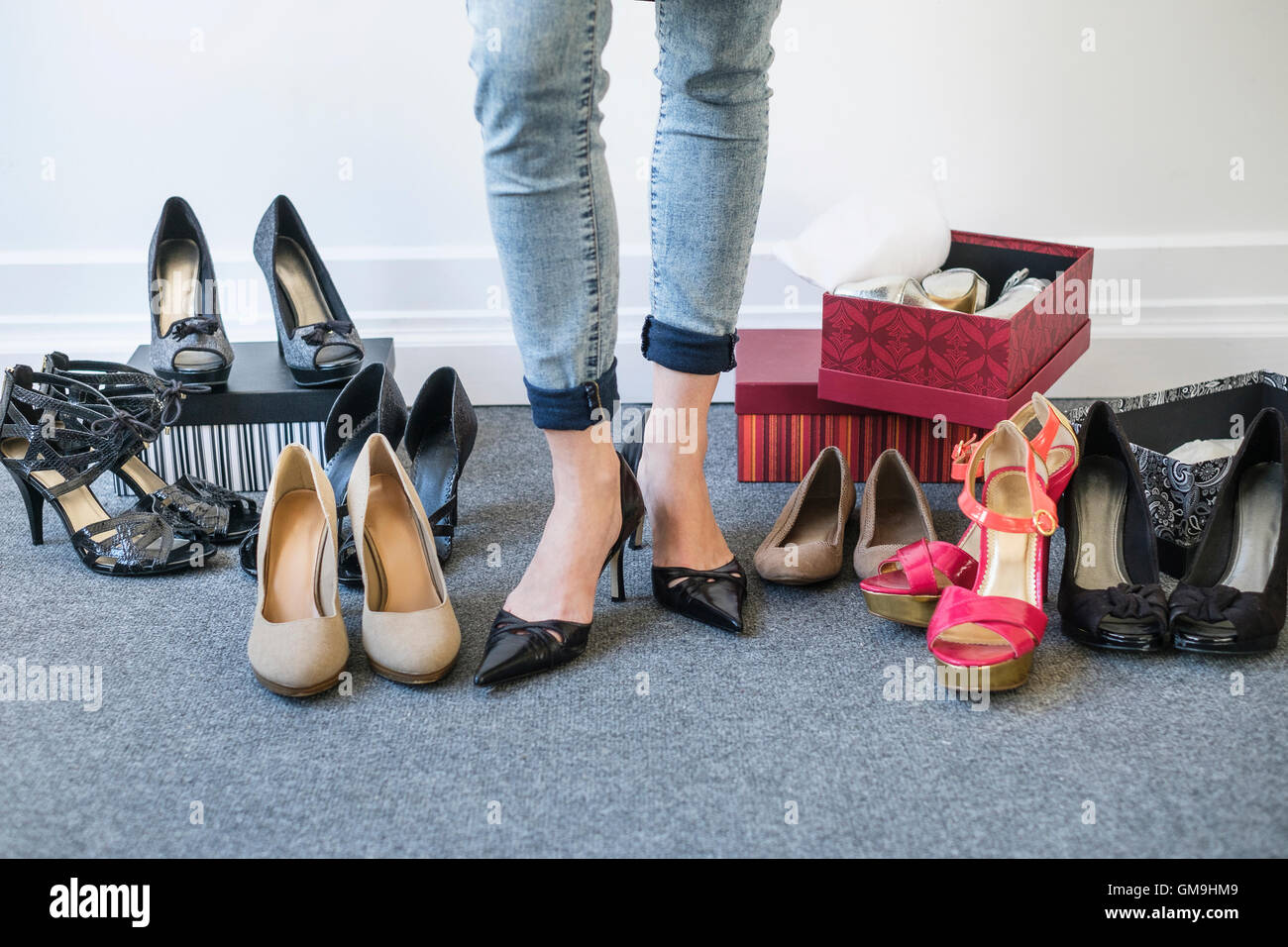 Woman trying on high heels on grey carpet - Stock Image