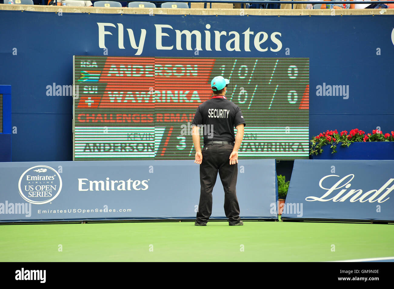 A security official standing in front of a score board at the 2016 Rogers Cup in Toronto, Canada. - Stock Image
