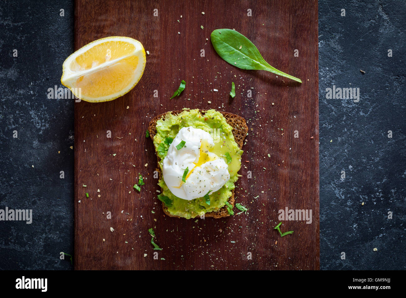 Avocado and poached egg sandwich on wooden cutting board, table top view healthy food - Stock Image