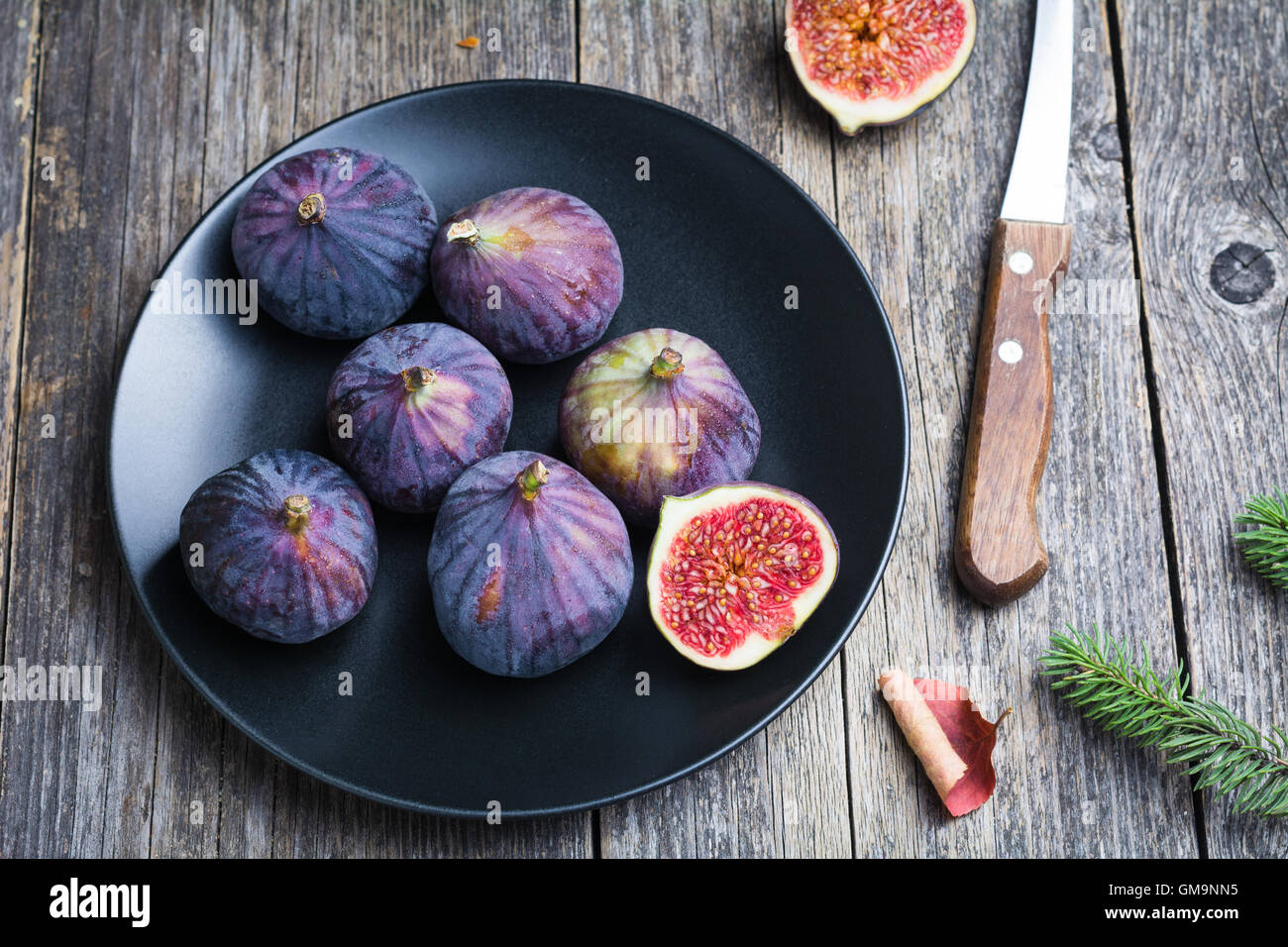 Fresh figs on black plate on wooden table - Stock Image