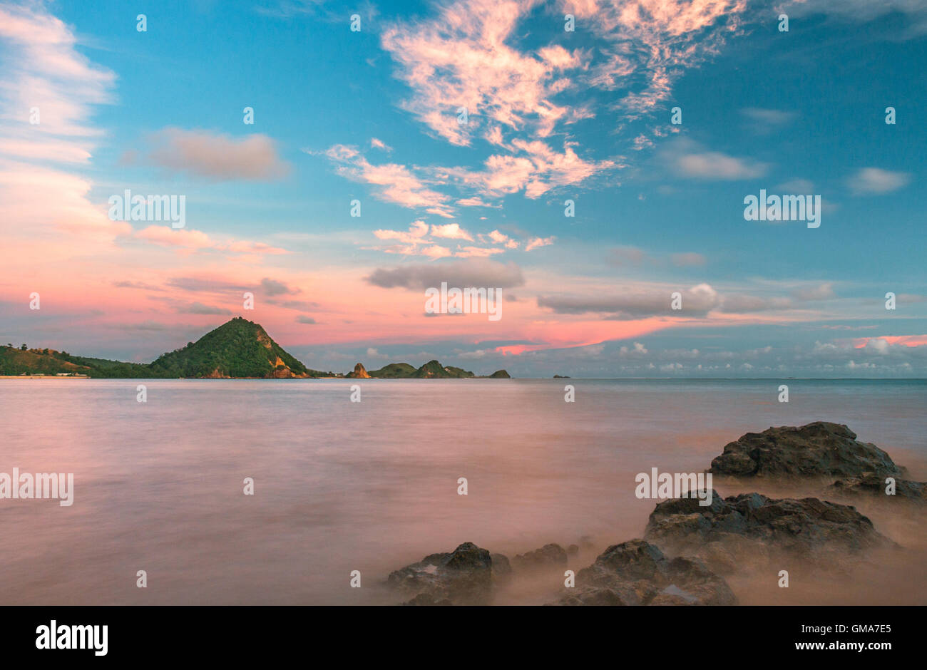 A long exposure of the still ocean and rocks, with a beautiful sky at sunset. - Stock Image