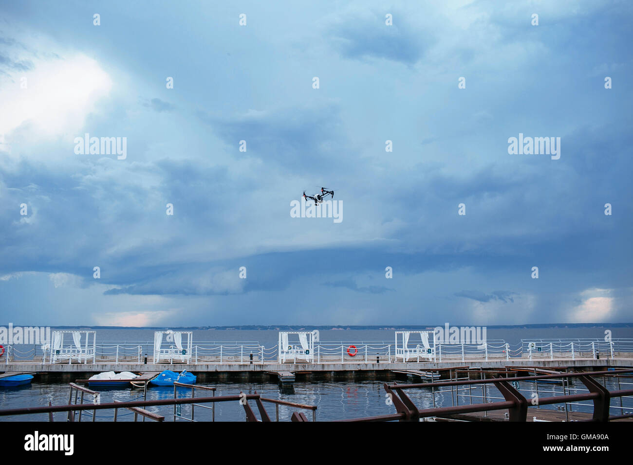 quadrocopter drone with remote control. thunderclouds storm, gloomily. stormy sky over the lake. - Stock Image