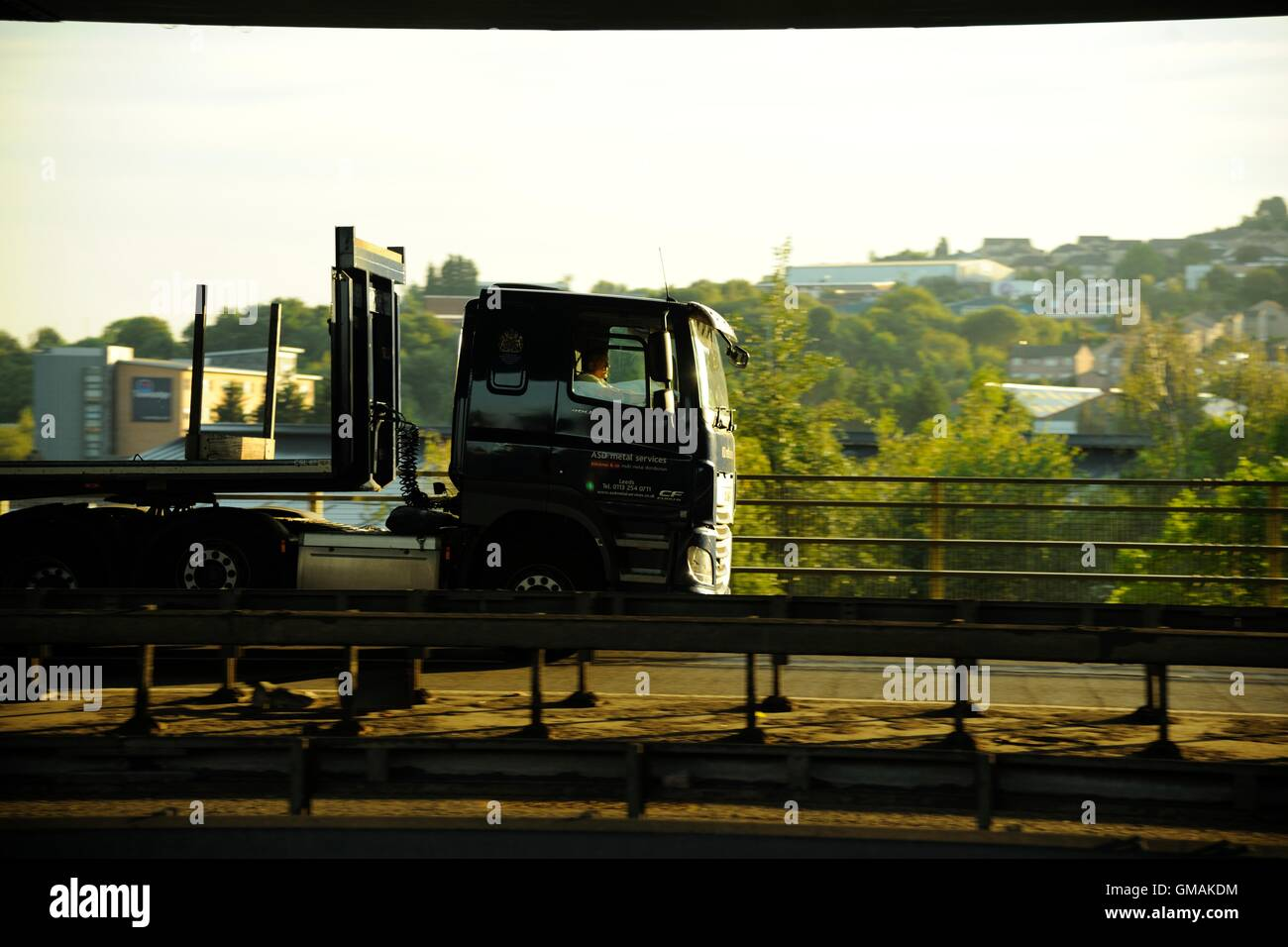 A DAF XF with flatbed steel-carrying trailer crosses Tinsley Viaduct, Sheffield near dusk - Stock Image
