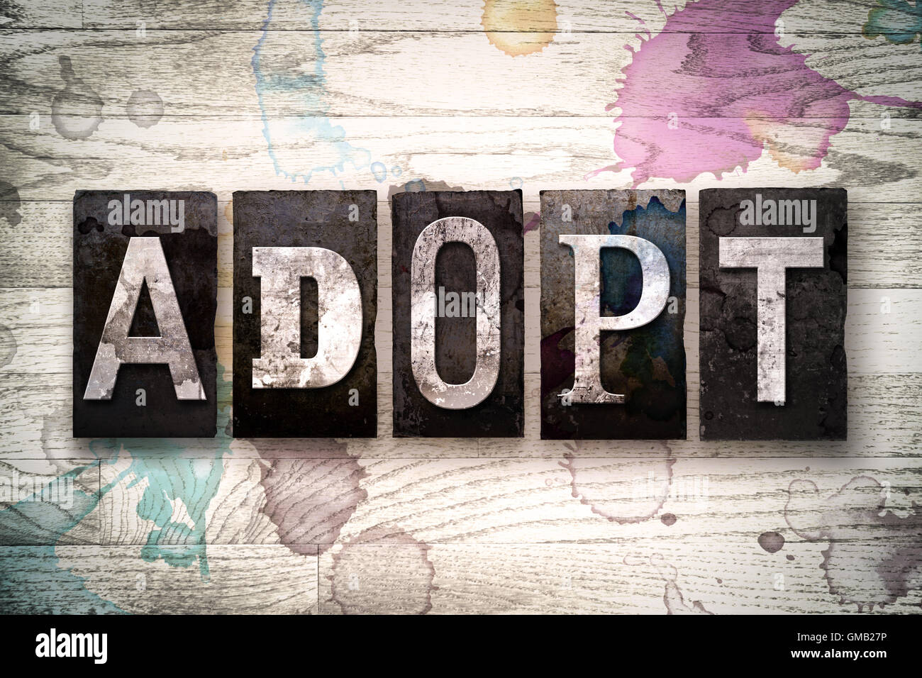 """The word """"ADOPT"""" written in vintage dirty metal letterpress type on a whitewashed wooden background with ink and Stock Photo"""