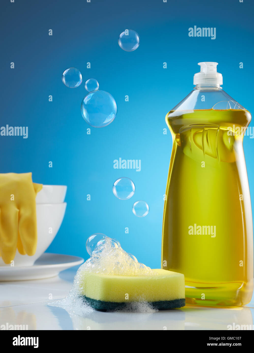 dishwashing products with bubbles, soap and crockery - Stock Image