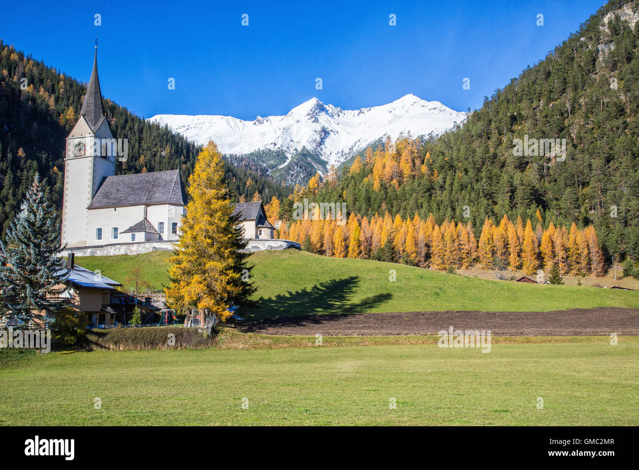 The church of Schmitten surrounded by colorful woods and snowy peaks Albula District Canton of Graubünden Switzerland Stock Photo