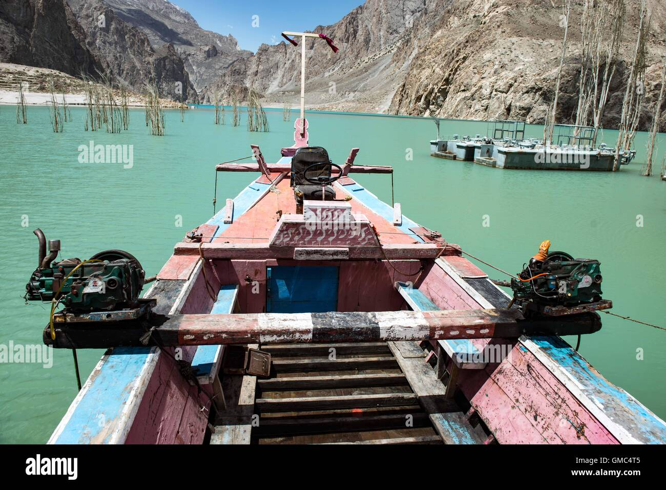 Redundant ferry boats and a pontoon on Attabad lake. The landslide that formed the lake is in the background. - Stock Image