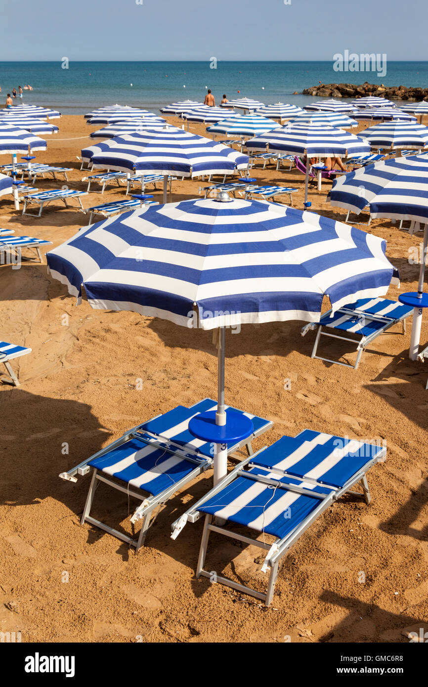 Sun umbrellas and sun beds on a beach, Marina Di Ragusa, Sicily, Italy Stock Photo