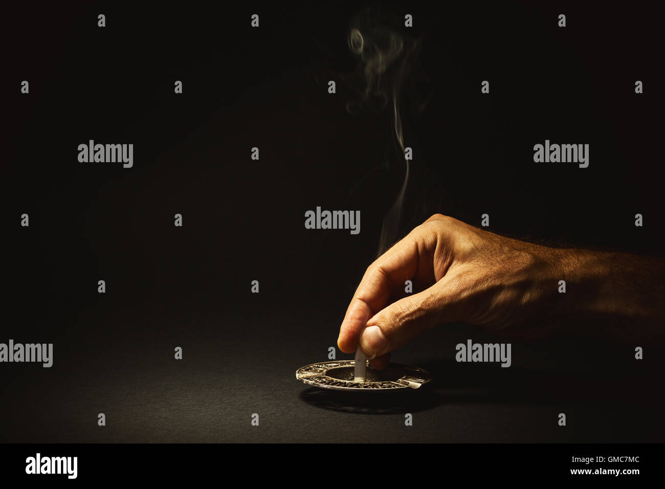 Conceptual composition about quit smoking, man's hand extinguishes a cigar. - Stock Image