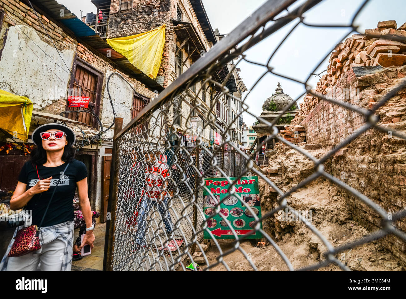 East asian tourist passes through an alley near a damaged historical building in Durbar Square, Kathmandu. © - Stock Image