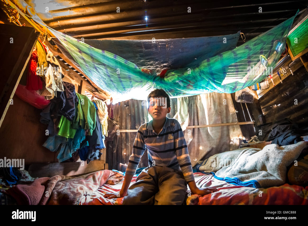 A boy sits in his bedroom on a temporary shelter in Kavrepalanchowk, Nepal. © Reynold Sumayku - Stock Image