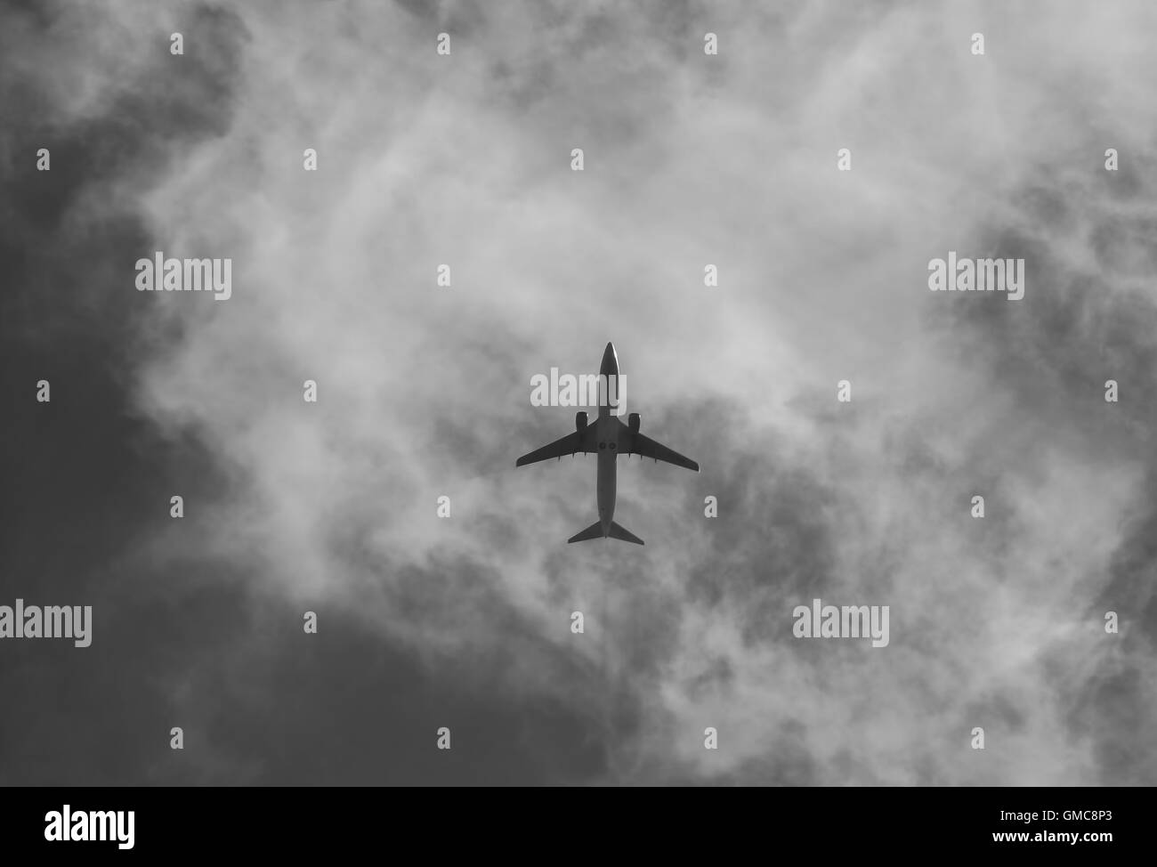 Civil aircraft cloud sky in black and white. - Stock Image