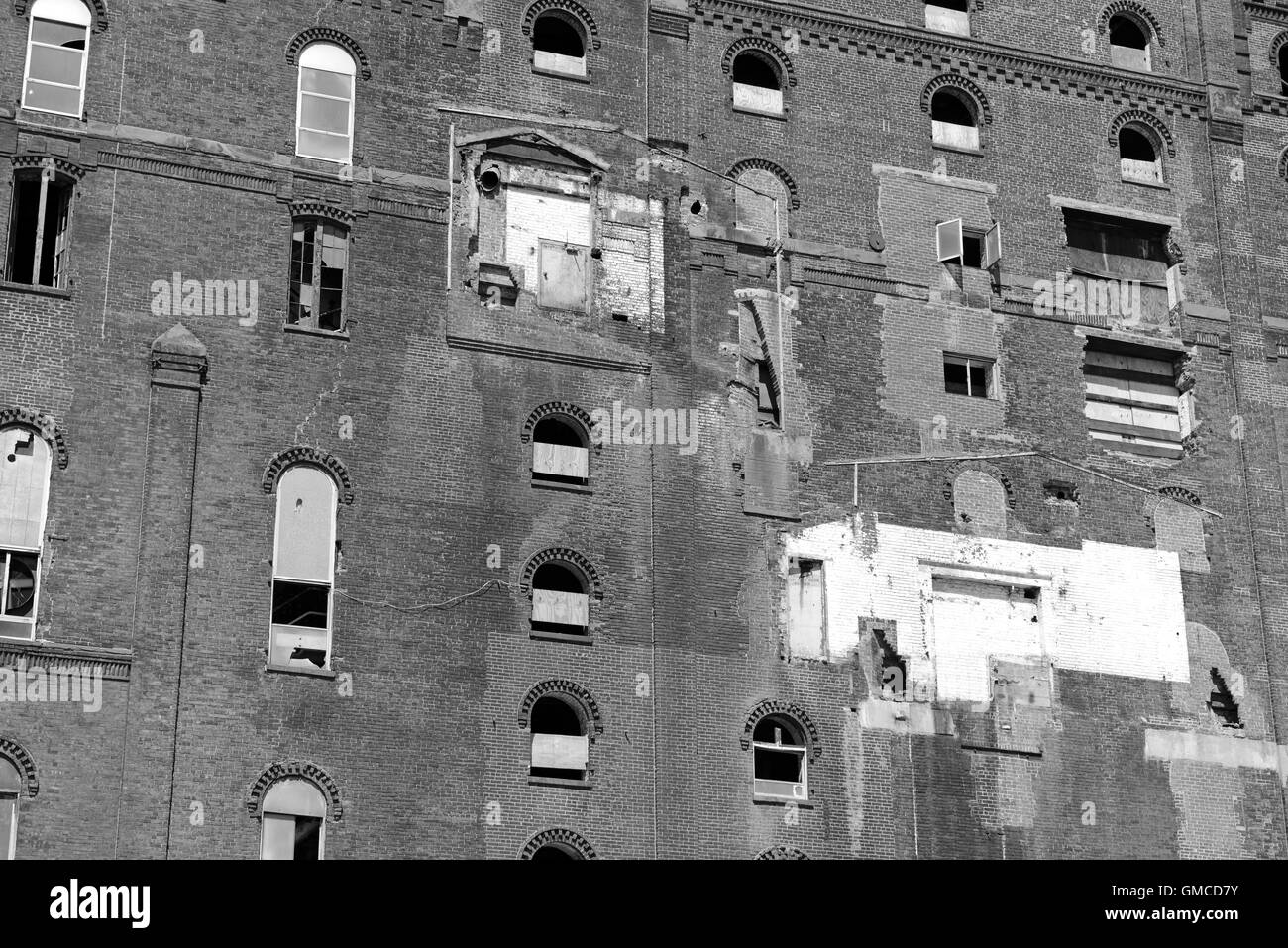 Abandoned brick building in lot with broken windows - Stock Image