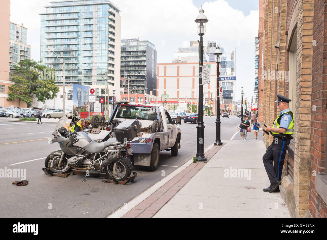 Motorbike Motorcycle being put on tow truck to be towed away - Front Street, Toronto, Canada - Stock Image