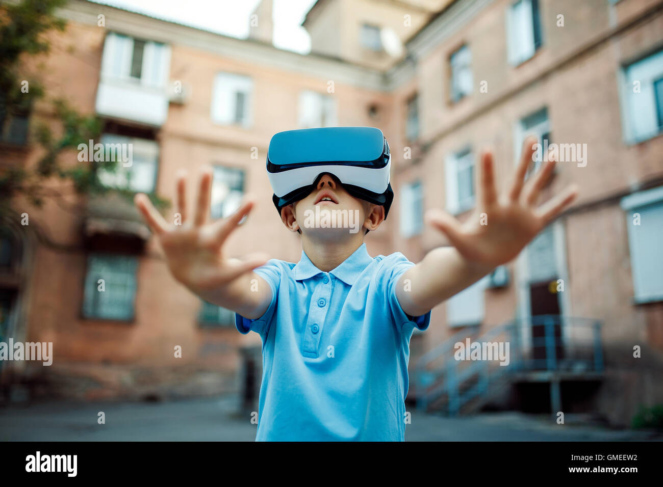 Fascinated little boy using VR virtual reality goggles. outdoor - Stock Image