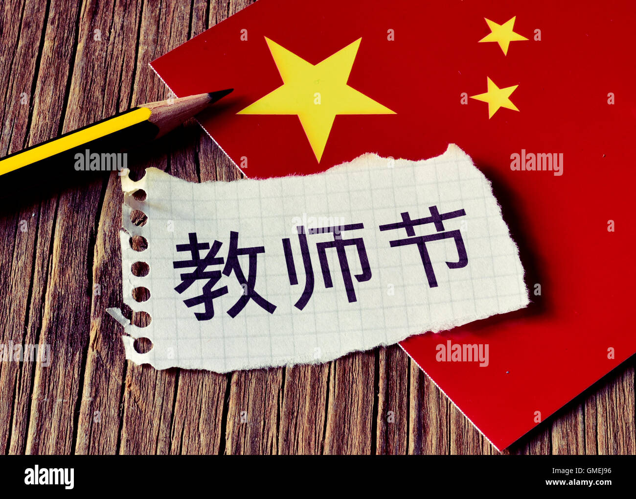 closeup of a peace of paper with the text Teachers Day written in Chinese, a pencil and the flag of China, placed - Stock Image