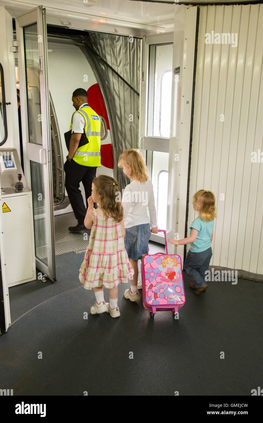 Child kid kids children / passengers board / boarding plane / airplane door. LHR London UK Heathrow airport / air - Stock Image