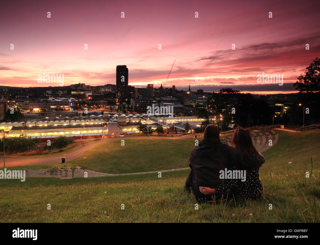 Sheffield, Yorkshire, UK. 26th Aug, 2016. A couple watch a stunning strawberry sunset from a hillside overlooking - Stock Image