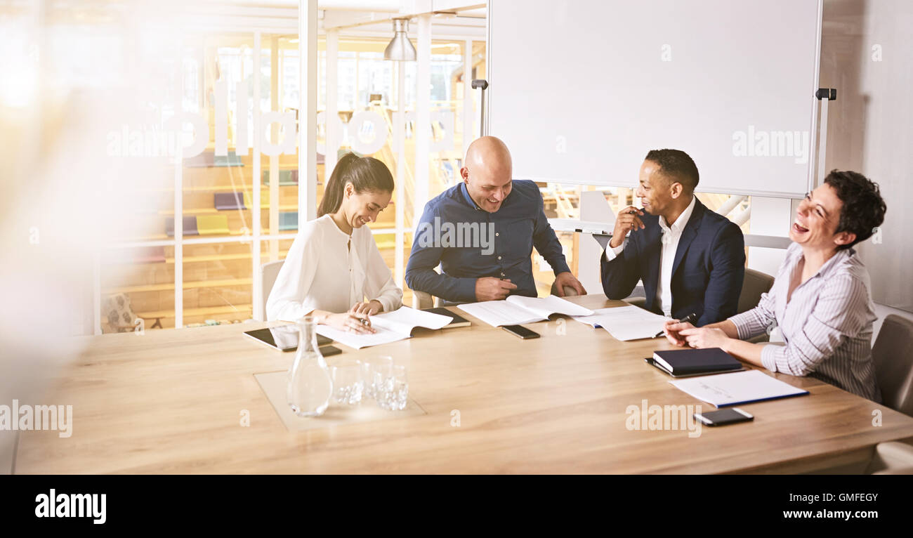 Four business people laughing during a professional board room meeting - Stock Image