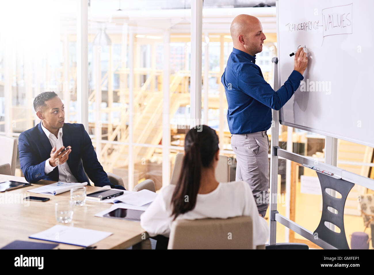 Young caucasian businessman writing company values on white board - Stock Image
