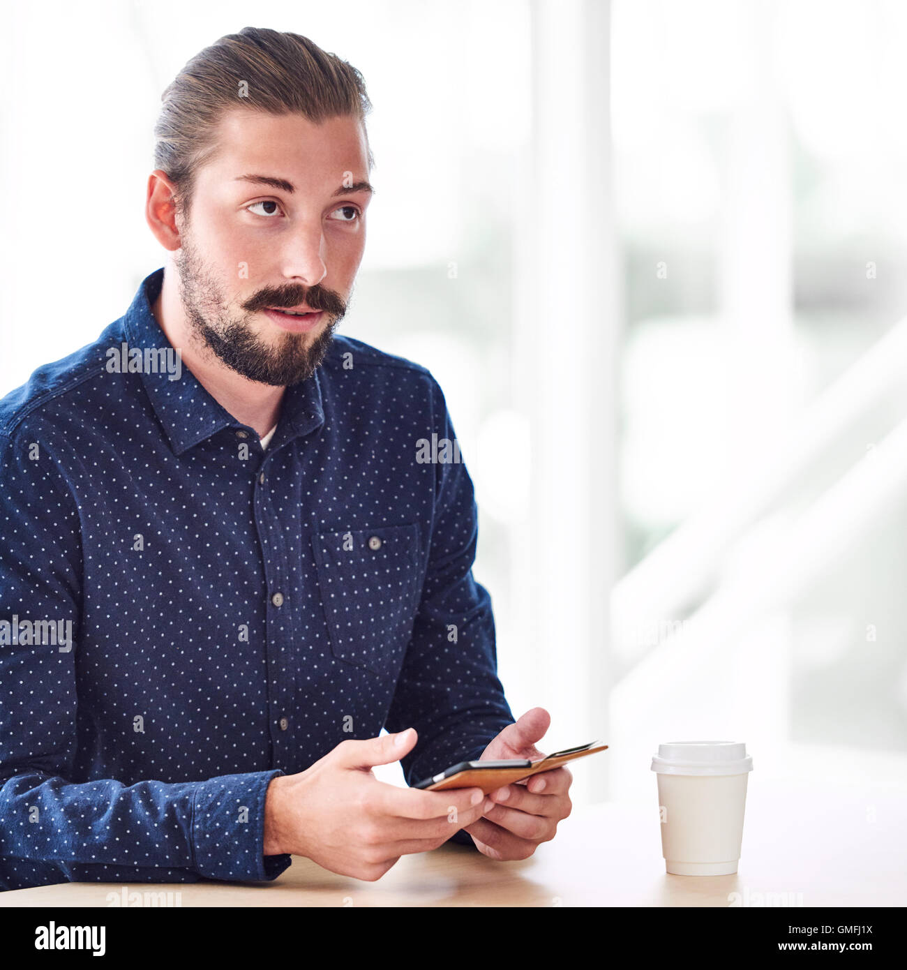long haired handsome man looking up while holding phone - Stock Image