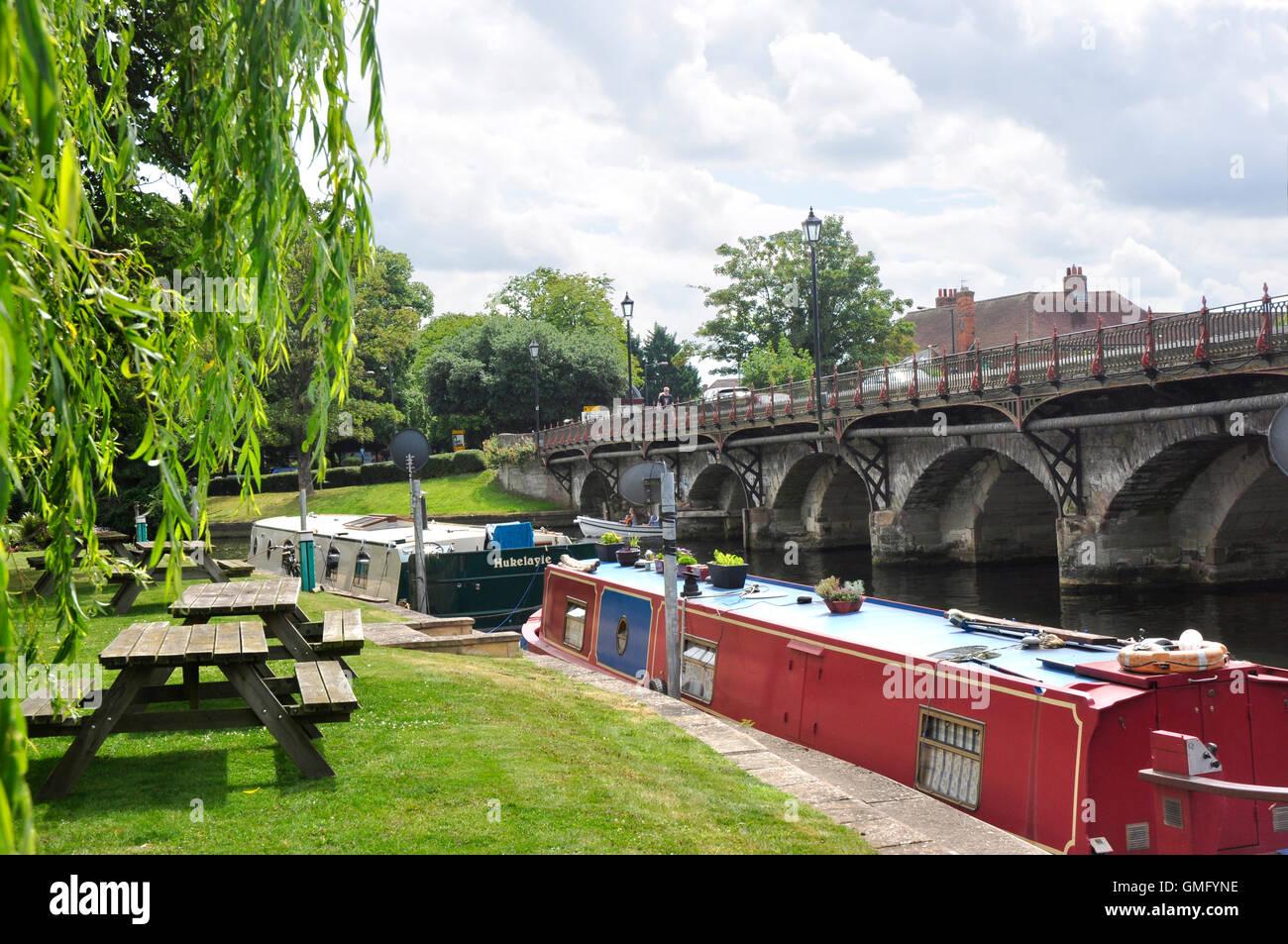 Warwickshire Stratford upon Avon - the marina - moored narrow boats - picnic tables - willow trees - backdrop town - Stock Image