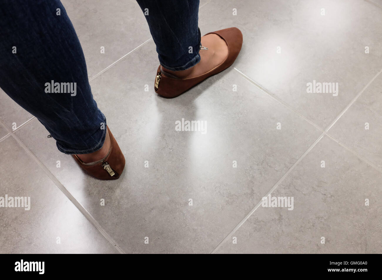 Feet of a woman standing with and zippered shoes - Stock Image
