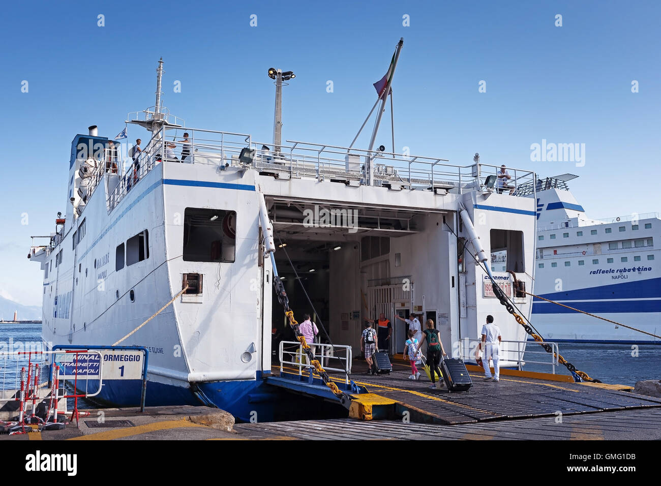 Naples, Italy - August 10, 2016: At the pier in the port of Naples, some tourists embark on the ferry to the island - Stock Image