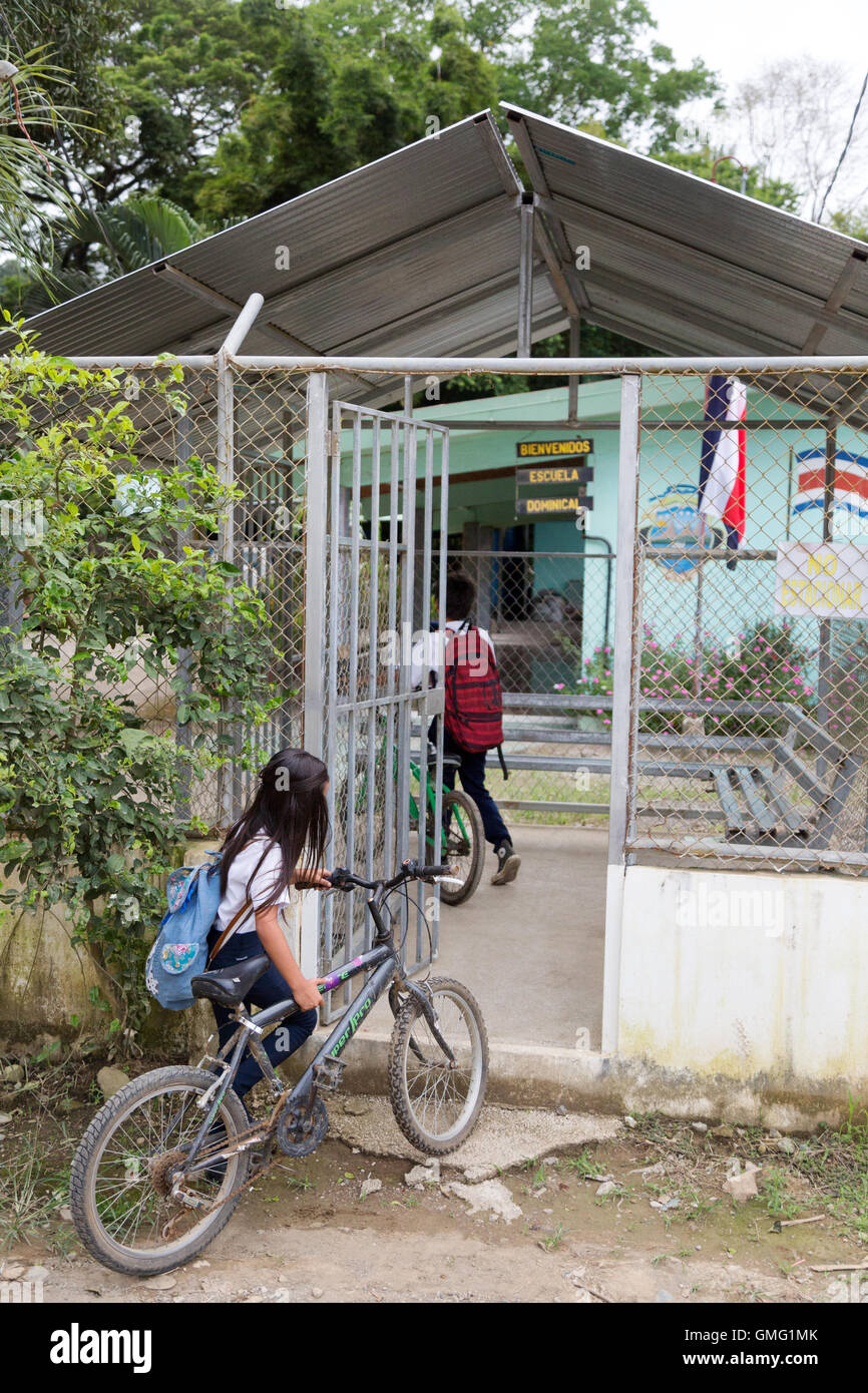 Children arriving at their school by bicycle, Dominical village, Costa Rica, Central America - Stock Image