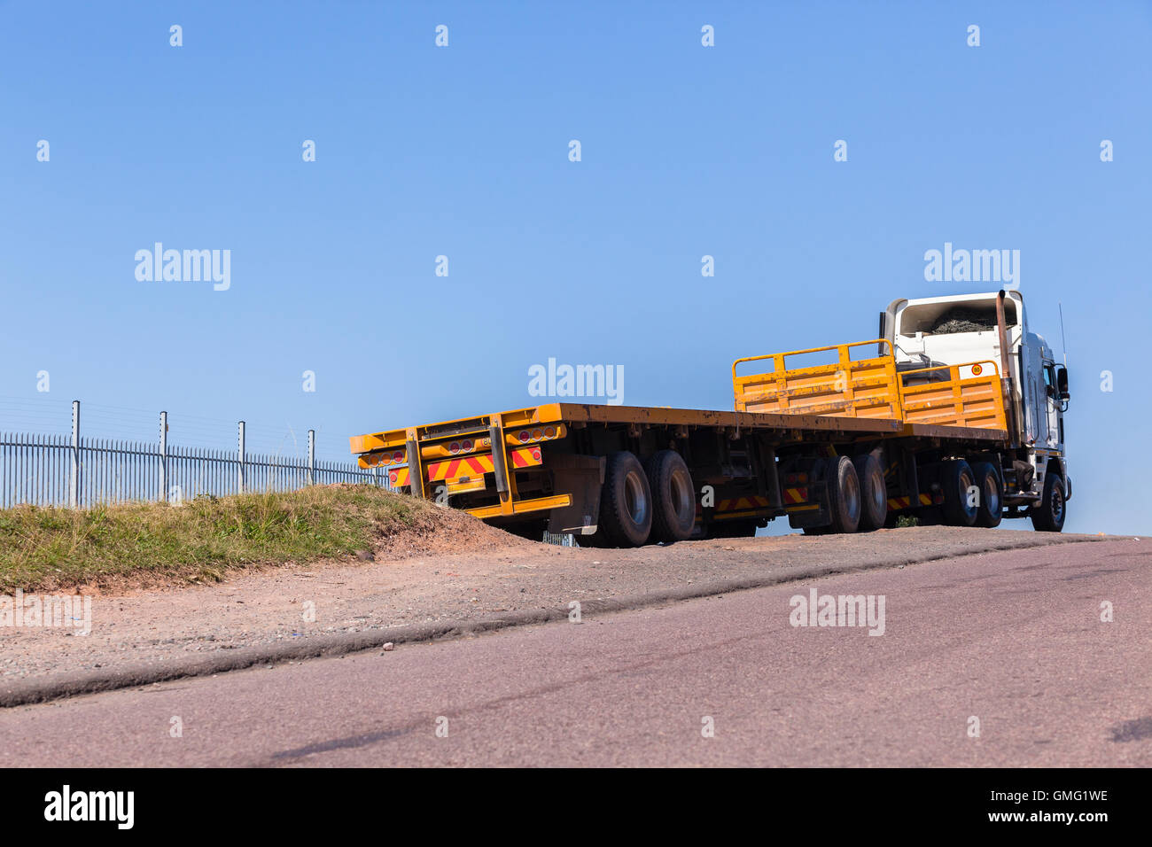 Truck vehicle with yellow trailers awaiting cargo to transport - Stock Image