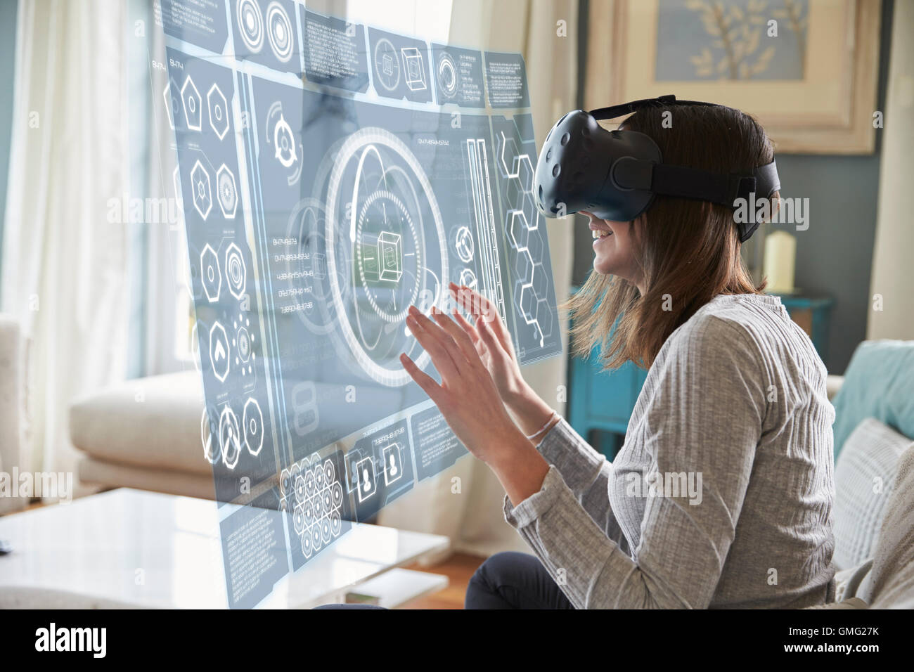 Woman Sits On Sofa At Home Wearing Virtual Reality Headset - Stock Image